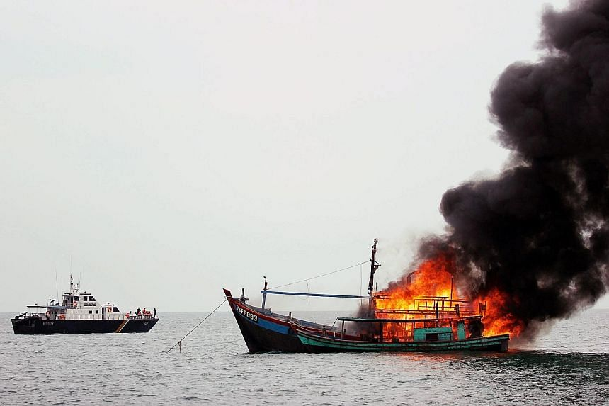 The Indonesian Navy supervising the destruction of a foreign vessel seized for fishing illegally in Indonesian waters near Belawan, north Sumatra, yesterday. According to media reports, Indonesia has sunk foreign boats across its territory as part of