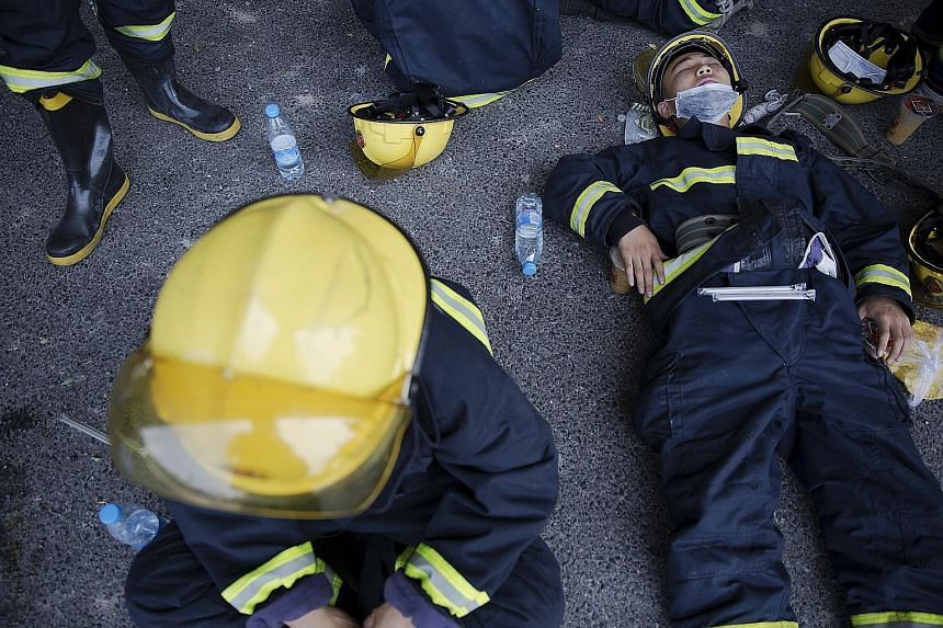Grieving family members (above) of firefighters killed in the Tianjin blazes at a makeshift memorial yesterday. Exhausted firefighters (left) taking a break from their dangerous task trying to control the inferno.