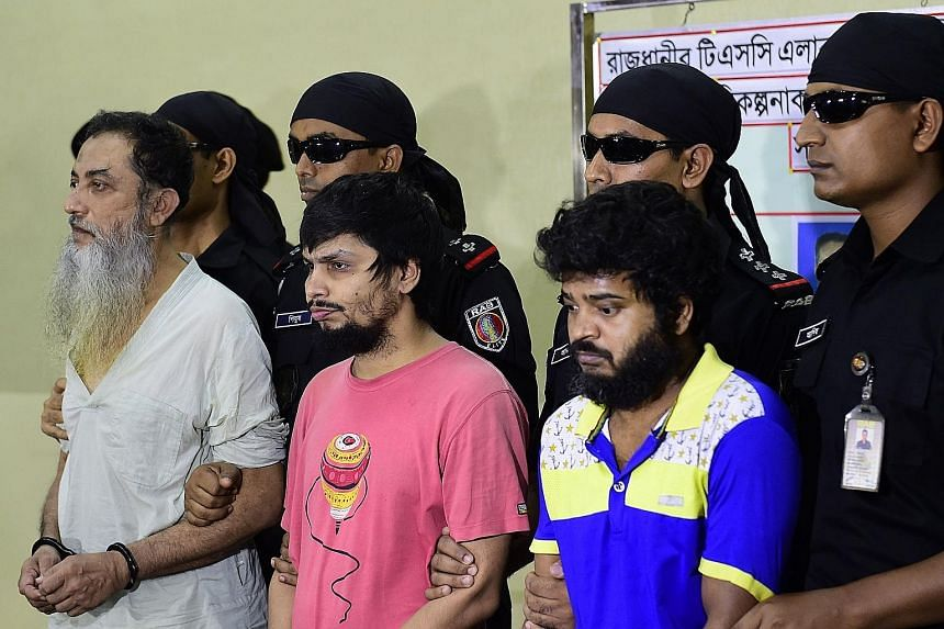 Security personnel with suspects (from left) Touhidur Rahman, Sadek Ali and Aminul Mollick at a media briefing in Dhaka yesterday. Police say Rahman, a British citizen, was the main planner of the killings.