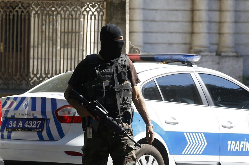 A member of the police special forces patrols the area after a shooting incident near the entrance to Dolmabahce Palace in Istanbul, Turkey  on Aug 19, 2015.