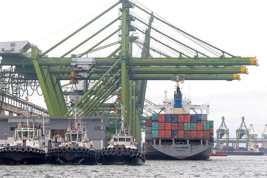 Quay cranes servicing a container ship berthed at the PSA Singapore Terminals Pasir Panjang.