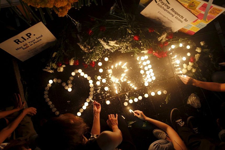 People lighting candles at the Erawan shrine, the site of Monday's deadly blast, in central Bangkok, Thailand, on Aug 18, 2015.