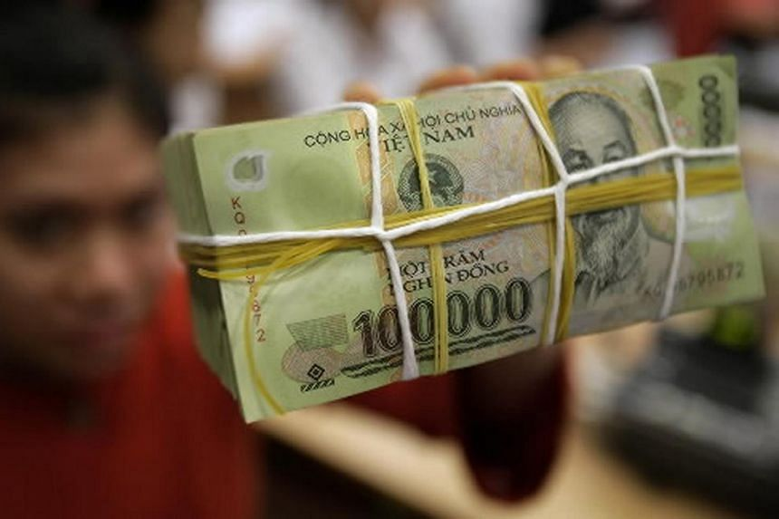Vietnam's central bank  lowered the official mid-point rate of the Vietnamese dong against the US dollar by 1 per cent on Wednesday, Aug 19.
