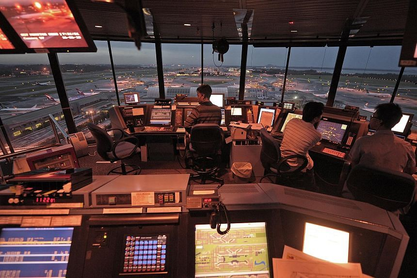 Air traffic controllers work inside the iconic Changi Airport control tower.