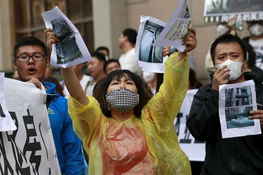 A resident evacuated from her home shouts slogans while holding images of her damaged house during a rally in Tianjin, China on Aug 19, 2015.