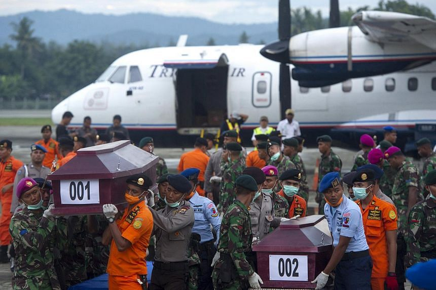 Indonesian security forces and rescue teams carry coffins containing the remains of some of the passengers recovered from the crash site on Aug 19, 2015.