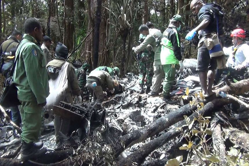 "Indonesian rescuers search through wreckage of the Trigana Air ATR 42-300 twin-turboprop plane at the crash site in the mountainous area of Oksibil on Tuesday. A plane that crashed in eastern Indonesia was found  ""completely destroyed"" with the bodie"