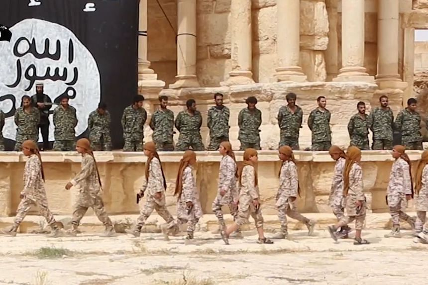 An image grab taken from a video made available by Jihadist media outlet Welayat Homs on July 4 this year allegedly shows 25 Syrian government soldiers kneeling as, what appears to be children or teenagers, wearing desert camouflage walk beneath them