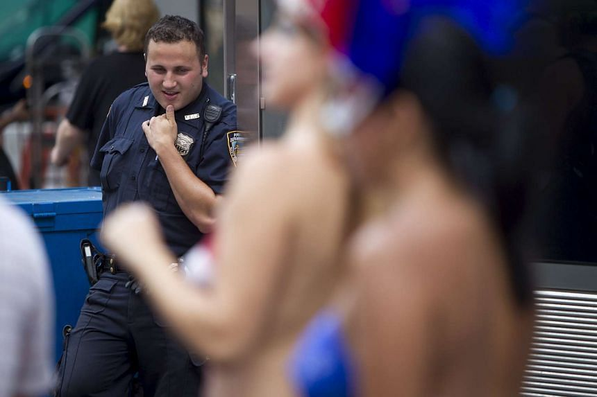 A policeman looks on as women who pose for tips wearing body paint and underwear are pictured in Times Square in New York.