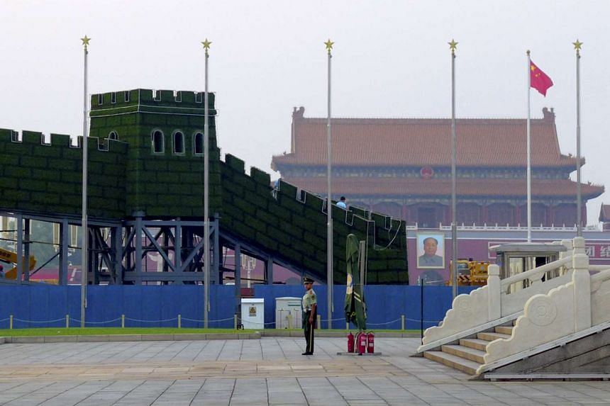 A paramilitary policeman stands in front of an installation on Tiananmen Square made to celebrate the upcoming military parade marking the 70th anniversary of the end of World War II, in Beijing on Aug 12, 2015.