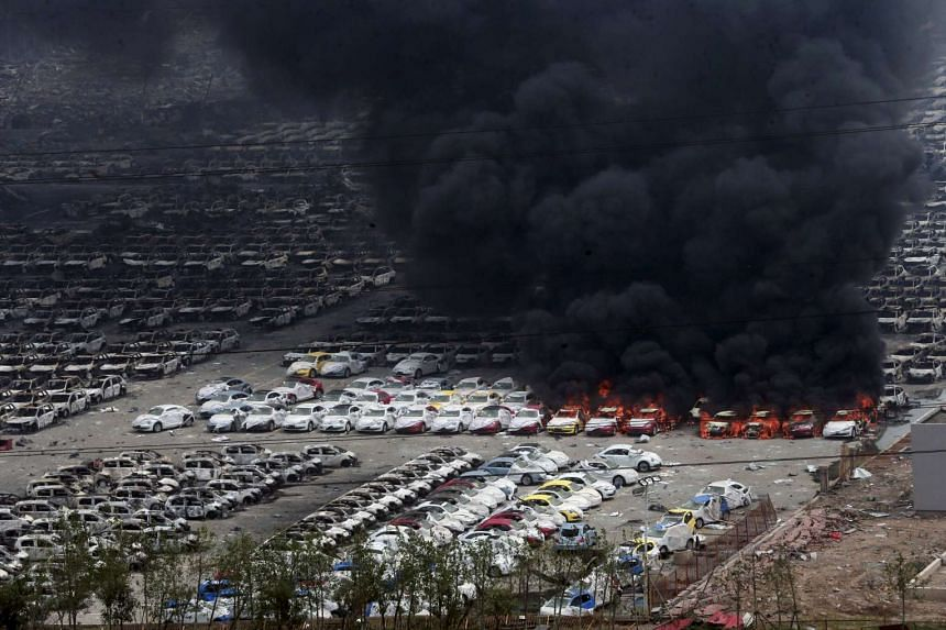 Smoke rises as damaged vehicles are seen burning at Binhai new district in Tianjin, China on Aug 15, 2015.