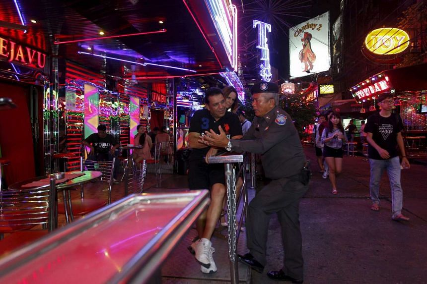 A police officer on patrol speaks with tourist at a bar in central Bangkok, Thailand, on Aug 19, 2015.