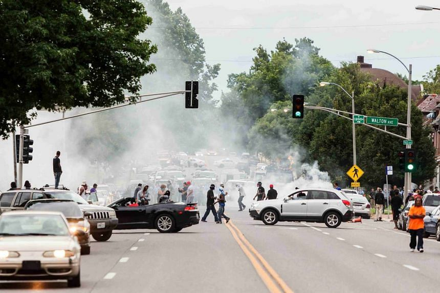 Smoke rises as police attempt to disperse protesters on Page Ave after a shooting incident in St. Louis, Missouri on Aug 19, 2015.