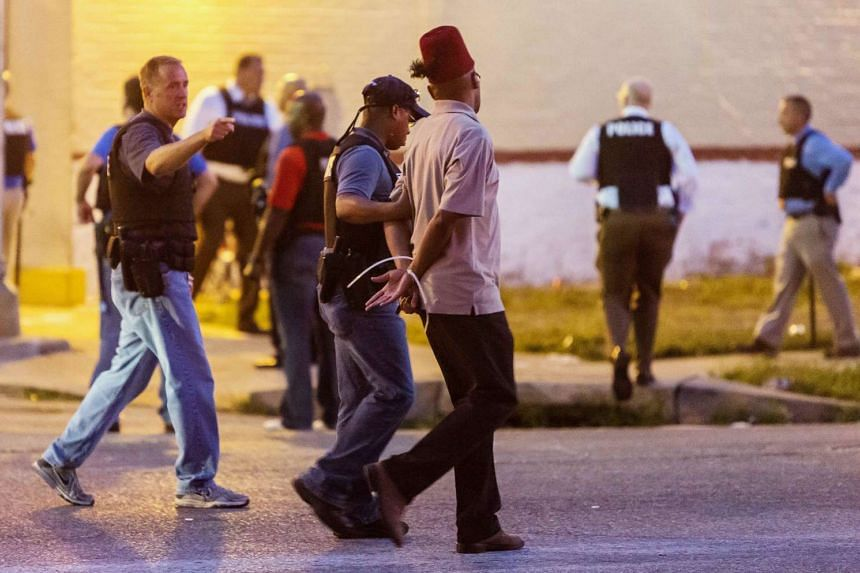 Police arrest a man as protesters gathered after a shooting incident in St. Louis, Missouri on Aug 19, 2015.