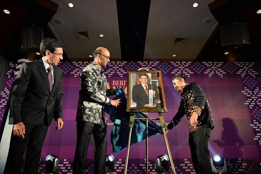 DPM Tharman Shanmugaratnam (centre) and Mr Mohd Saat Abdul Rahman (right), editor of Malay daily Berita Harian, unveiling a portrait of Mr Mohammad Alami Musa (left), this year's Berita Harian Achiever of the Year, at the award ceremony last night.