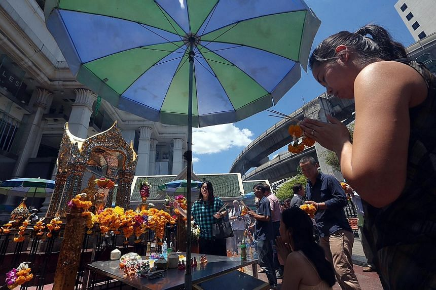 Visitors praying at Erawan Shrine in Bangkok after it reopened yesterday morning, less than 48 hours after the bomb attack on Monday night. A constant stream of people turned up yesterday to offer flowers and notes in memory of the victims. The Thai