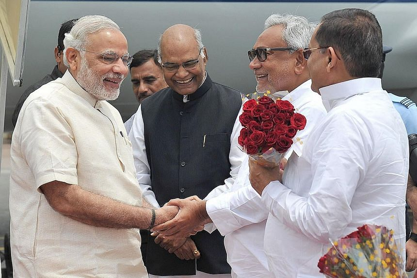 India's Prime Minister Narendra Modi (left) being greeted by Bihar's Chief Minister, Mr Nitish Kumar (second from right), and Governor Ram Nath Kovin (in black) upon his arrival in the state on Tuesday.