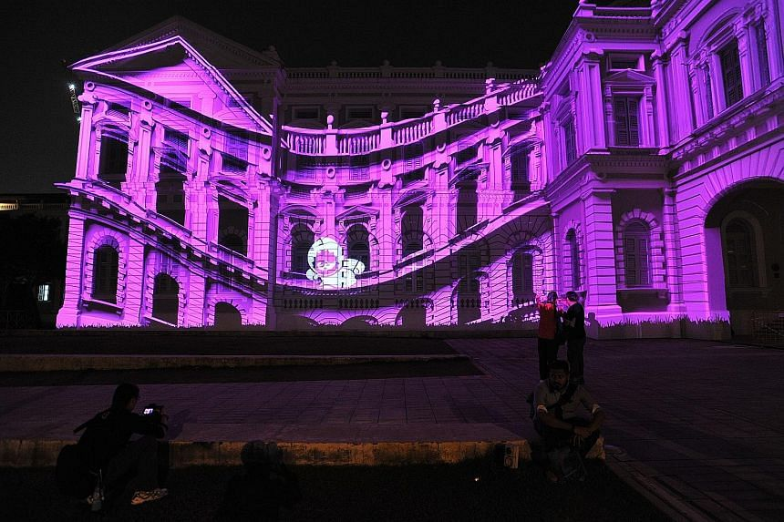"The facade of the National Museum comes alive with animated characters Anook and Nooki, the world's smallest Inuits. They are part of a light art installation entitled ""The Anooki Celebrate Singapore"" by David Passegand and Moetu Batlle from France."
