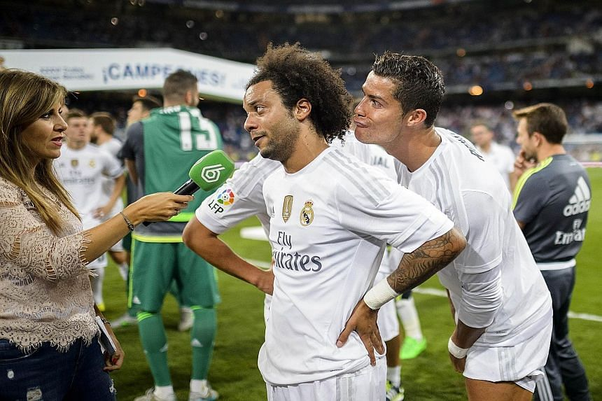 Cristiano Ronaldo (right) channels his inner prankster as Real Madrid team-mate Marcelo speaks to a journalist after their side's 2-0 victory over Galatasaray in Madrid on Tuesday.