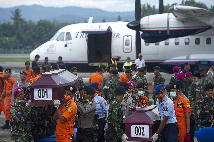 Indonesian security forces and rescue teams carrying coffins containing the remains of some of the passengers recovered from the crash site of the Trigana Air plane yesterday at Sentani Airport, near Jayapura, Papua province.