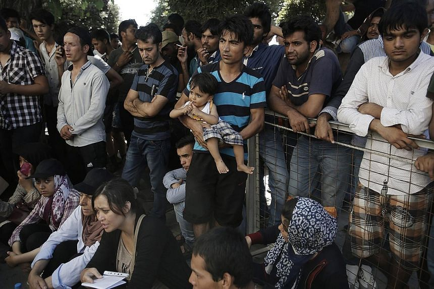 Pakistani and Afghan migrants awaiting registration outside a police station on the Greek island of Kos yesterday. Some 250,000 migrants have already crossed the Mediterranean this year to Italy and Greece. The number is expected to pass 300,000 by e