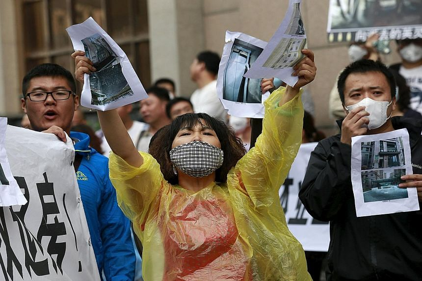 Evacuated residents, armed with pictures of damage to their homes, shouting slogans during a rally outside the venue of a government official's news conference in Tianjin yesterday. Around 150 homeowners demanded the government buy back their apartme