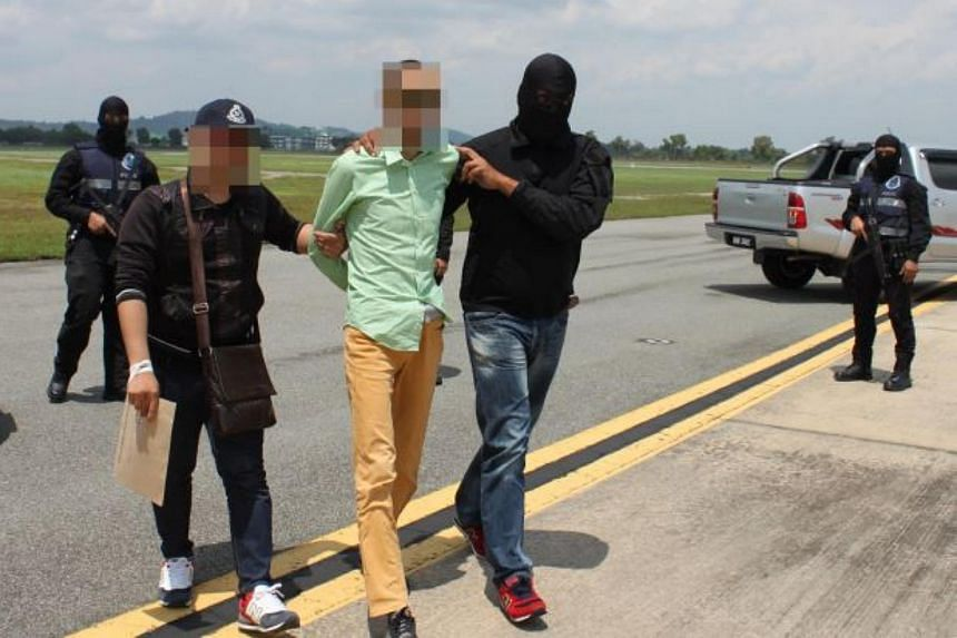 Bukit Aman Counter Terrorism Division personnel detaining a suspected ISIS member on Wednesday.