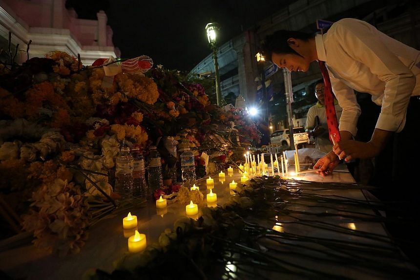 A man lights a candle at a small makeshift tribute area outside Erawan Shrine to remember the victims of the Monday bomb blast in Bangkok.