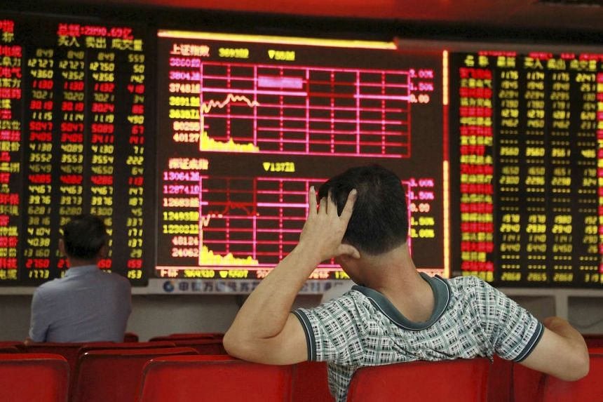 Investors look at an electronic board showing stock information at a brokerage house in Haikou, Hainan province, China on Aug 19, 2015.