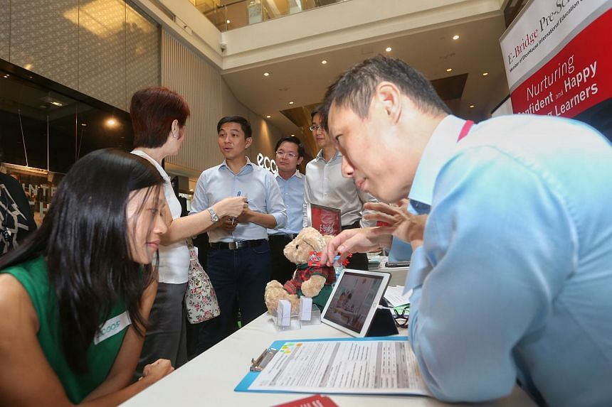 Minister for Social and Family Development Tan Chuan-Jin touring the booths at an early childhood recruitment fair, which introduces a new training programme for educarers (who work with children aged two months to three years), at 313@Somerset on 20