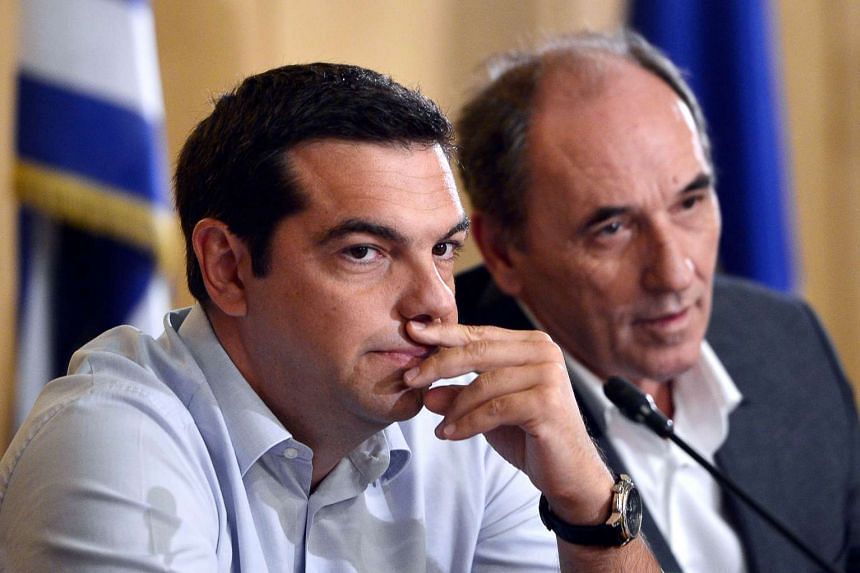 Greek Prime Minister Alexis Tsipras (left, with Greek Economy Minister Giorgos Stathakis) is considering holding early elections after the austerity bailout split his radical left Syriza party.