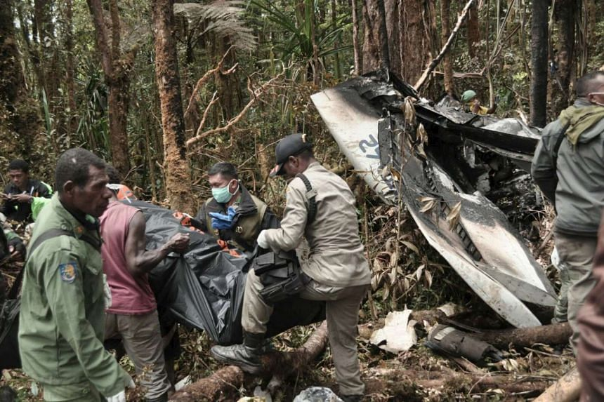 Rescue team members carrying bodies of the victims of the crashed Trigana Air at the crash site near Oksibil, Bintang Mountains district, Papua province, Indonesia.