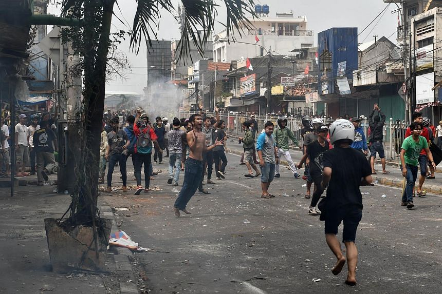 Residents clash with police and civil security personnel during a demolition of some 150 shanty houses in Jakarta on Aug 20, 2015.