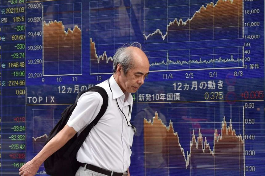 A man passing by a share prices board in Tokyo on Aug 19, 2015.