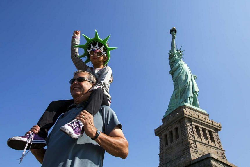 A girl mimics the Statue of Liberty as she poses for photos in front of the US landmark.
