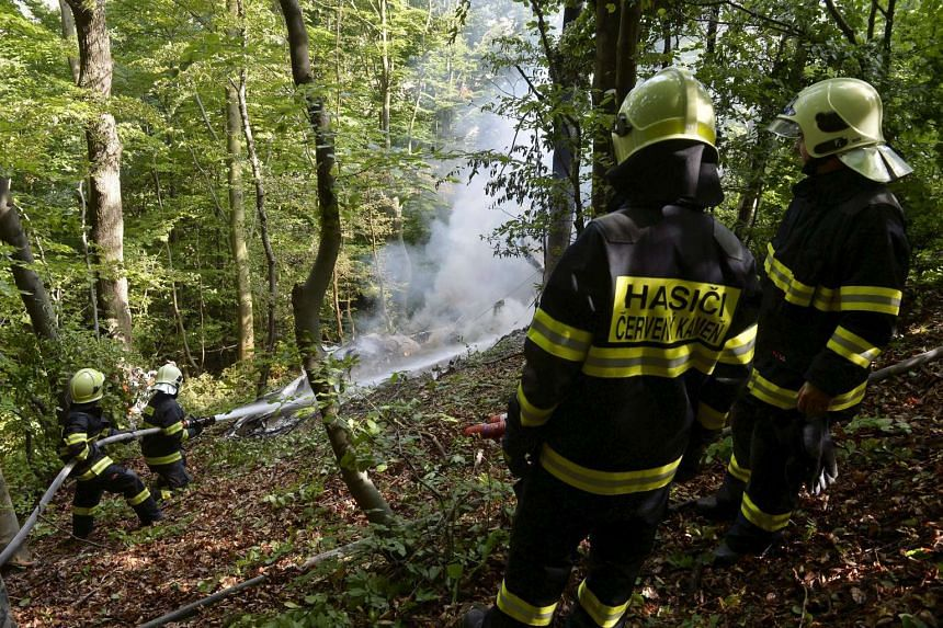Firefighters work at the crash site of two sport planes near the village of Cerveny Kamen, Slovakia on Aug 20, 2015.
