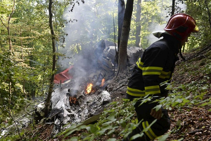 A firefighter inspects the crash site of two sport planes near the village of Cerveny Kamen, Slovakia on Aug 20, 2015.