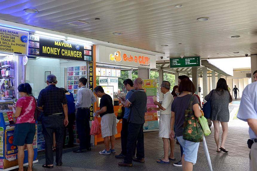 Singaporeans queuing to exchange money at Mayura Money Changer at Toa Payoh Central.