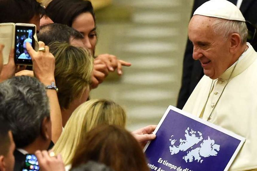 Pope Francis holds a sign about the Falkland Islands during his weekly general audience on Aug 19, 2015, at the Vatican.
