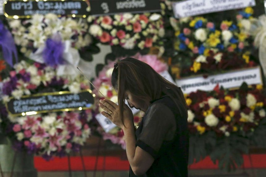 A victim's relative prays during a Buddhist funeral at a temple in Nonthaburi province, on the outskirts of Bangkok.
