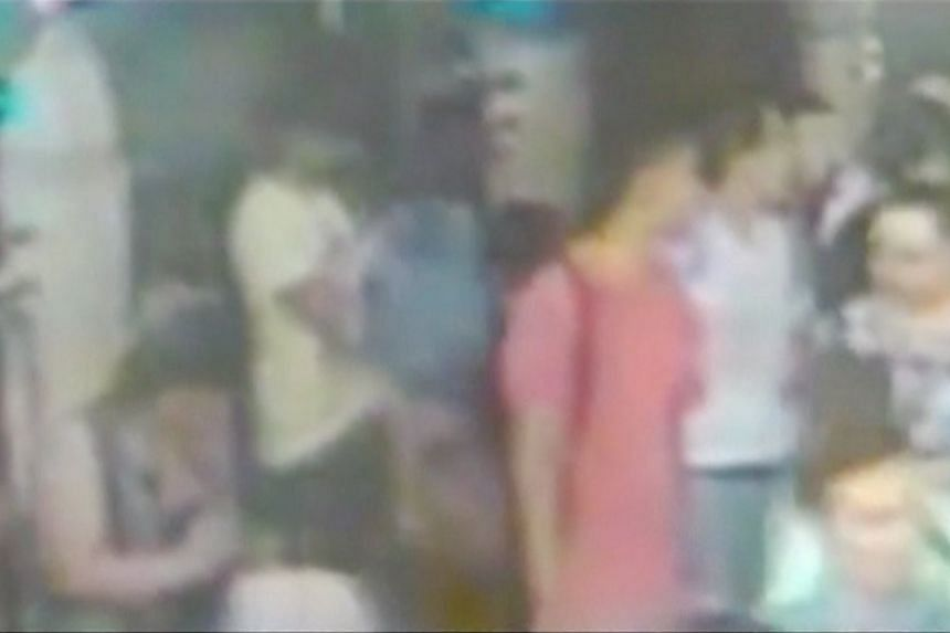 A still CCTV image shows two new suspects - dressed in red (centre) and white (third right) - standing in front of a previously identified suspect in a yellow t-shirt removing his backpack prior to the blast.