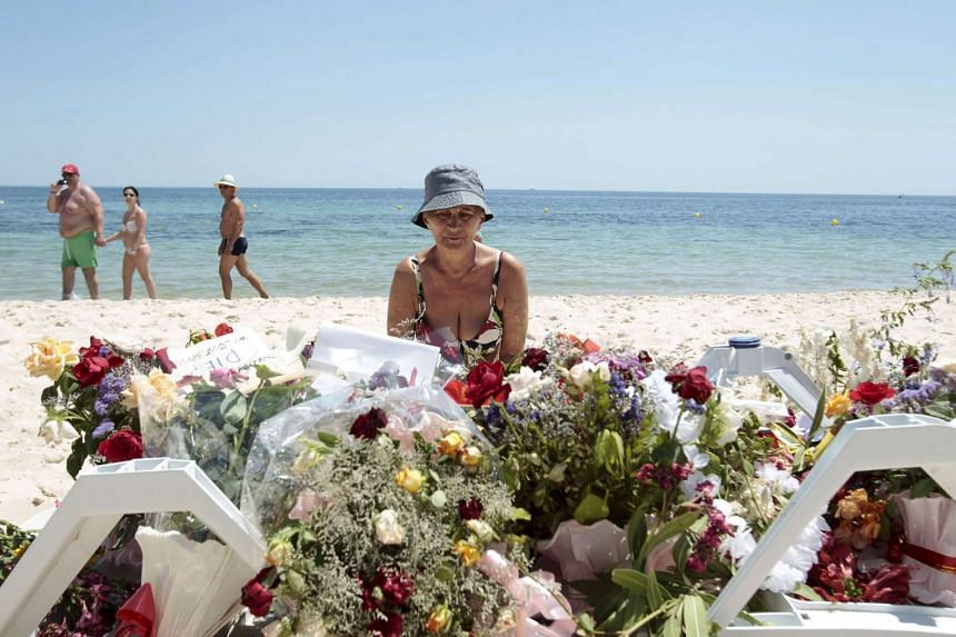 A tourist sits near flowers placed after a gunman killed 39 foreigners in Sousse, Tunisia, in June 2015.