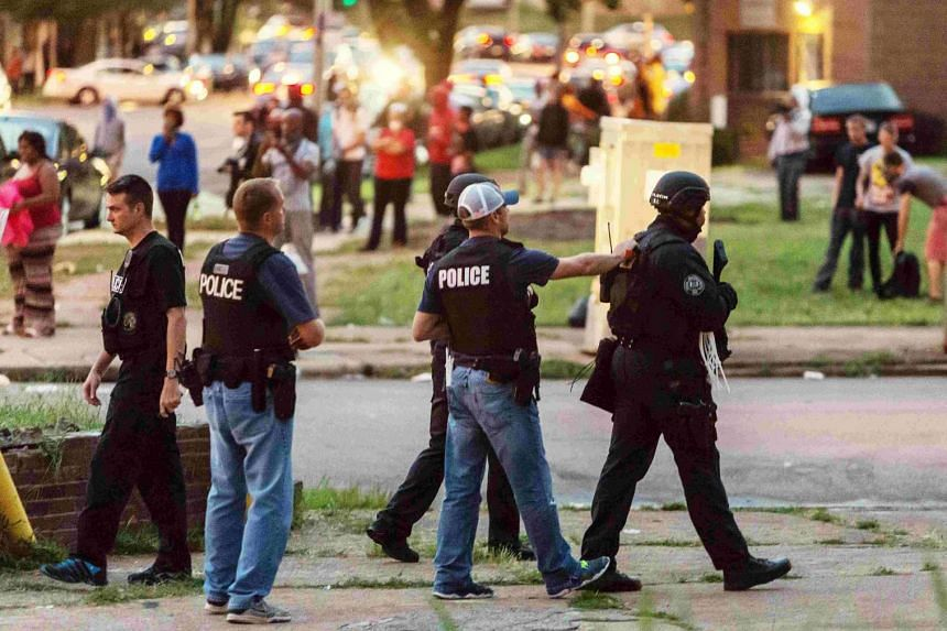 Police monitor the crowd as protesters gathered after a shooting incident in St. Louis, Missouri on Aug 19, 2015.