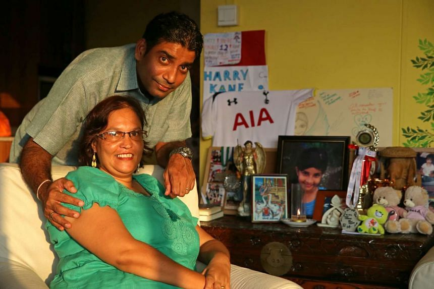Mr Jaidipsinh Jhala and his wife Karen next to a table filled with photos, trophies and other items belonging to their daughter Sonia that was put up in the living room of their home.
