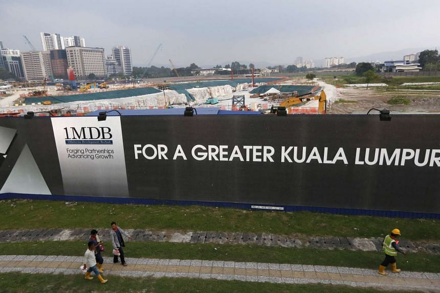 Men walking past a 1MDB billboard at the funds flagship Tun Razak Exchange development in Kuala Lumpur, Malaysia.