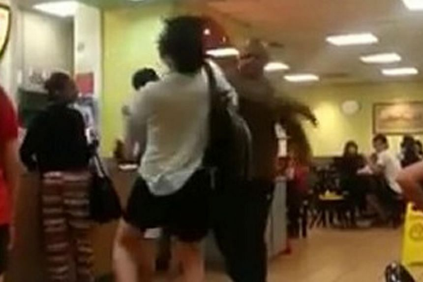 The video starts with one man in a white T-shirt and carrying a black backpack shouting at another man in a brown shirt. It leads to both men exchanging blows before a customer steps in to separate them.