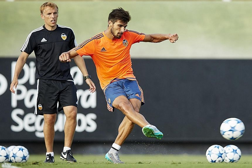 Valencia's assistant manager Phil Neville (left) watching young midfielder Andre Gomes making a pass during training. The Spanish La Liga football club have kept their promising players together in the belief that they will help bring success in Spai