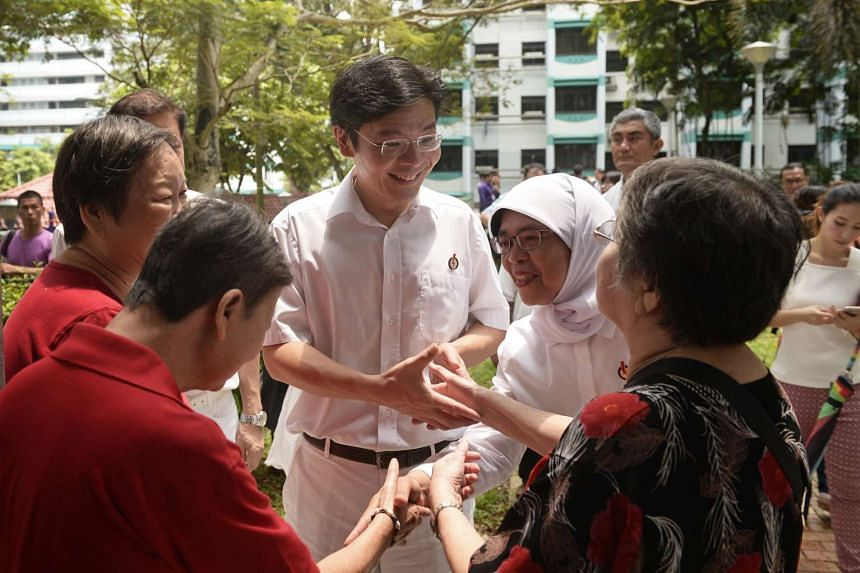 Lawrence Wong and Halimah Yacob, the co-anchors for the PAP's Marsiling-Yew Tee team, greeting residents.