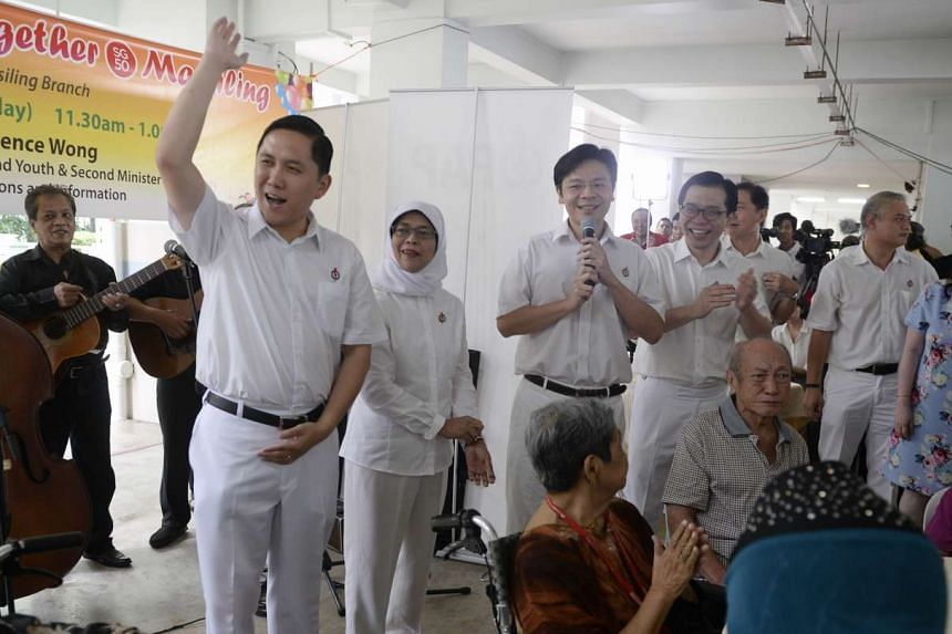 The PAP's team for the new Marsiling-Yew Tee GRC (from left) Alex Yam, Halimah Yacob, Lawrence Wong and Ong Teng Koon greeting residents at the Marsiling block party.