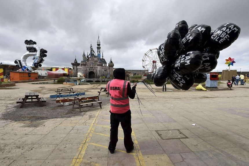 A performer holds a bunch of balloons at Dismaland, a theme park-styled art installation by British artist Banksy.